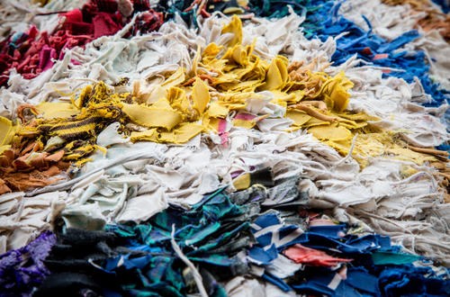 An image of textile scraps in a landfill shows how waste is a real apparel industry issue that requires innovative solutions.